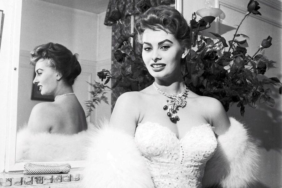Le 8ème Festival de CANNES se déroule du 26 avril au 10 mai 1955 : plan de face de Sophia LOREN (souriante) prenant une attitude sexy dans sa suite du Carlton, portant une parure de 160 diamants en collier et une robe du soir décolletée et pailletée de 700 000 lires.