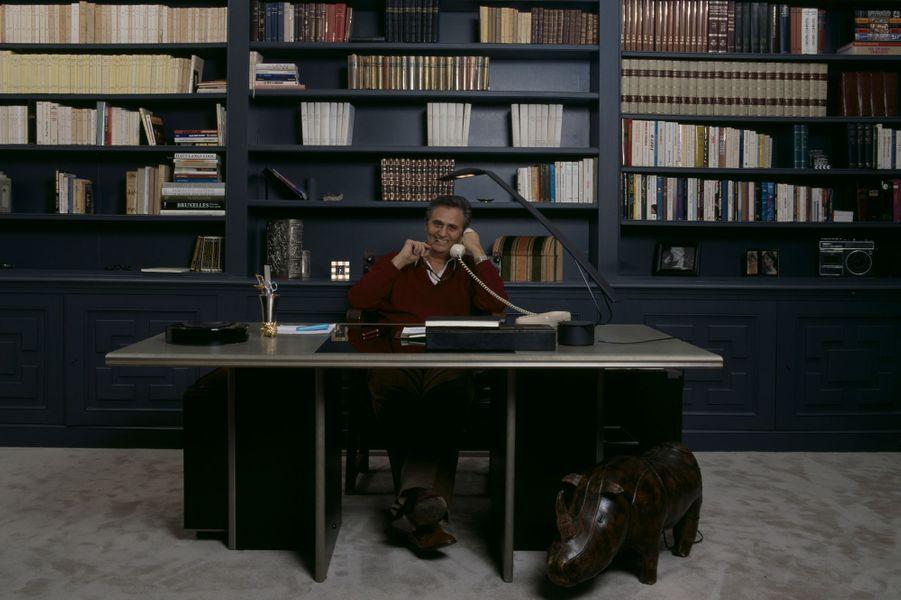 En France, à Paris, en février 1987, Roger HANIN, acteur, chez lui, assis sur son bureau, devant sa bibliothèque.