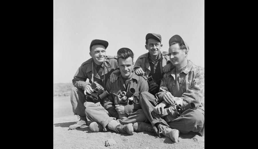 Les photographes du SPI (Service presse information) , Paul Corcuff, Jean Péraud et du SCA (Service cinématographique de l'armée), Pierre Schoendoerffer et André Lebon posent avec leur matériel au camp retranché de Na San. 1952.