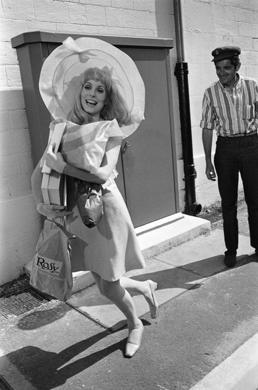 """Jacques DEMY coiffé d'une casquette regardant en souriant Catherine DENEUVE en robe et capeline, chantant et dansant des paquets plein les bras avant le tournage d'une scène en extérieur du film """"Les demoiselles de Rochefort""""."""