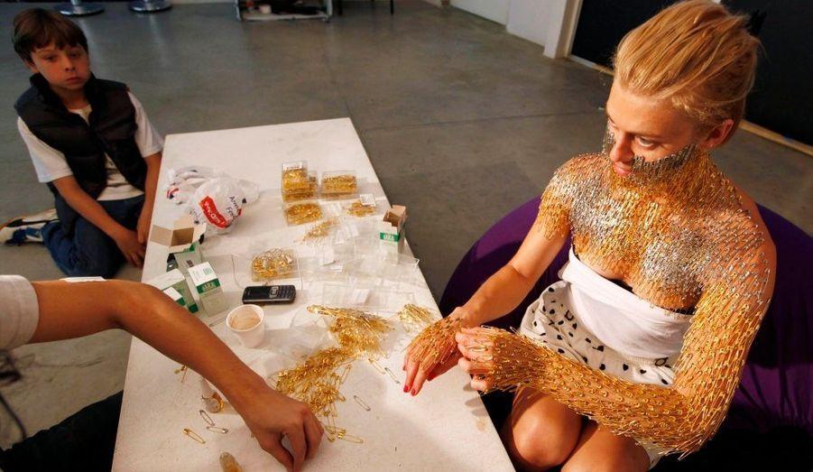 """Un visiteur observe l'artiste australienne Lucy McRae en train de coller à la glue des épingles à nourice sur son propre corps, pendant le """"Rojo Nova work in progress"""", au Musée de l'image et du son de Sao Paulo."""