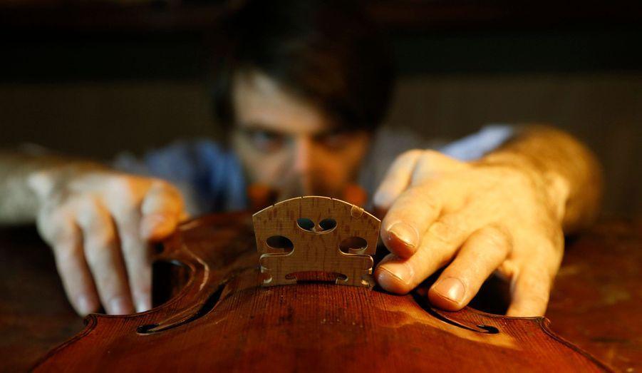 Le luthier français Mathias Menanteau répare un violon dans son atelier dans le centre de Rome.