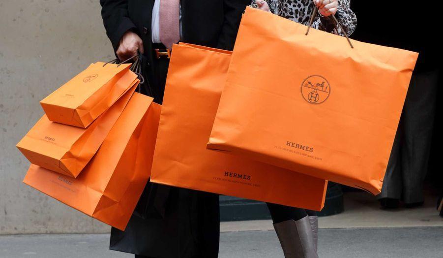 Un couple sortant d'Hermès à Paris. Le sellier a enregistré un nouveau record de ventes en 2012, à 3,48 milliards d'euros (+22,6%), supérieur à ses attentes et à celles des analystes, et la marge opérationnelle va elle aussi battre le record de 31,2% établi en 2011, selon un communiqué publié mardi.