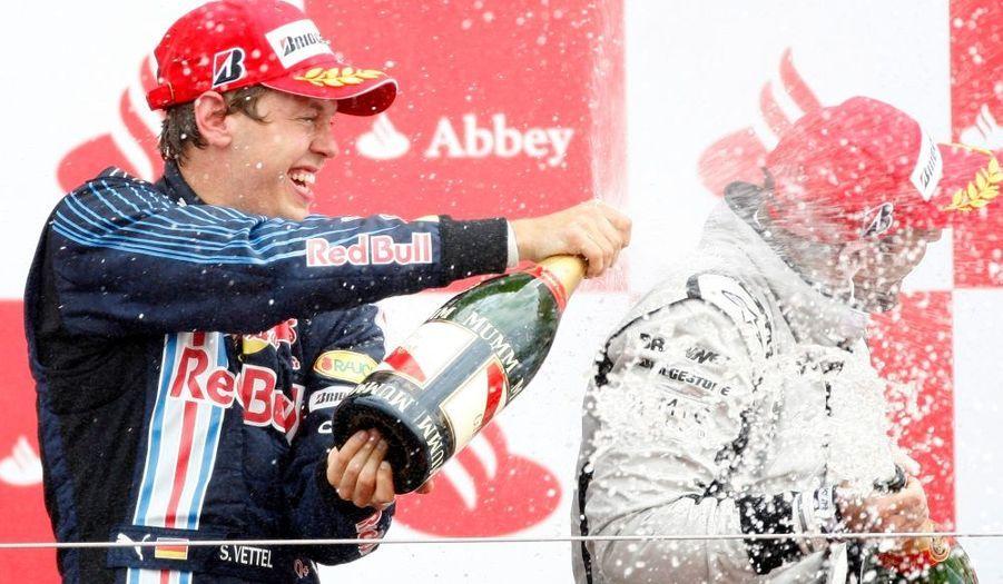 Le pilote britannique de F1 Sebastian Vettel savoure sa victoire de ce dimanche lors du grand prix de Silverstone. Aux anges, il arrose de champagne Rubens Barrichello, classé troisième.