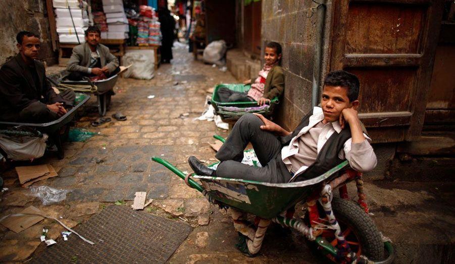 Des hommes et des enfants attendent l'arrivée de livraisons au marché de Sanaa, au Yémen.