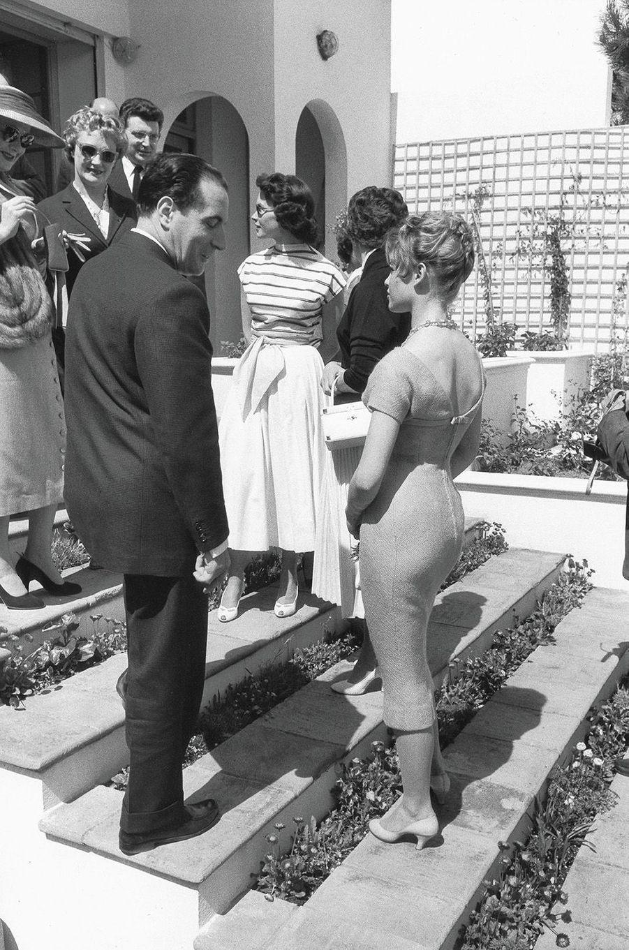 Le ministre François Mitterrand à Cannes pour déclarer l'ouverture du Festival de cinéma. Il ne peut s'empêcher d'admirer les formes de Brigitte Bardot dans une robe moulante.