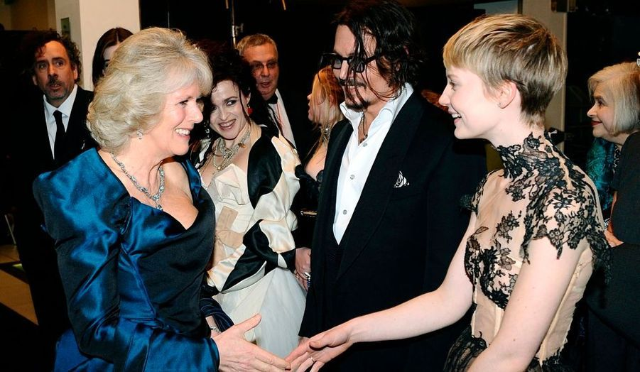 Camilla, la Duchesse de Cornwall, s'est rendue à la première d'Alice au pays des merveilles hier à Londres. Elle salue ici Mia Wasikowska, qui est aux côtés de l'acteur principal du nouveau film de Tim Burton, Johnny Depp.