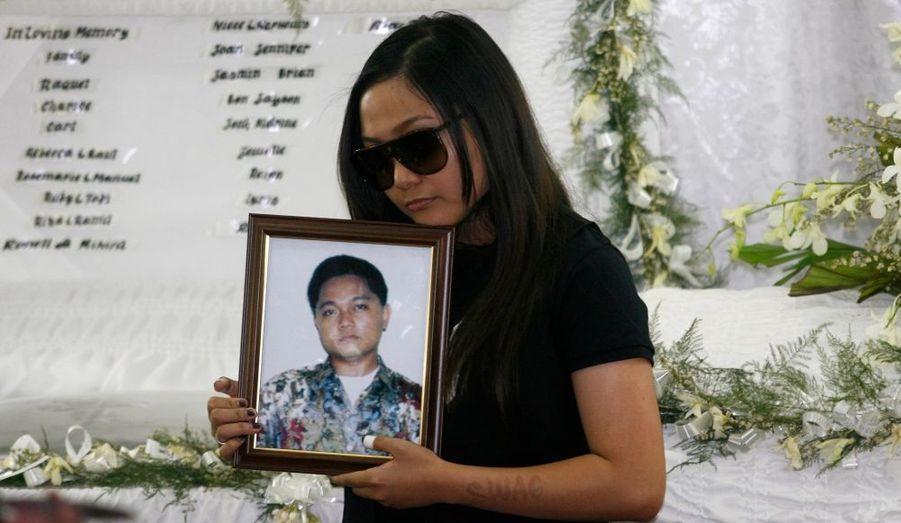 """La chanteuse et star de """"Glee"""" Charice Pempengco porte le portrait de son père, lors de l'enterrement de ce dernier, à Muntinlupa City, dans le sud de Manille. Le père de Charice a été poignardé dans la rue."""