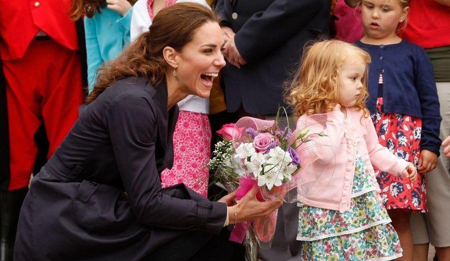 Kate, la Duchesse de Cambridge, éclate de rire après avoir reçu des fleurs lors d'une visite à Summerside, au Canada.