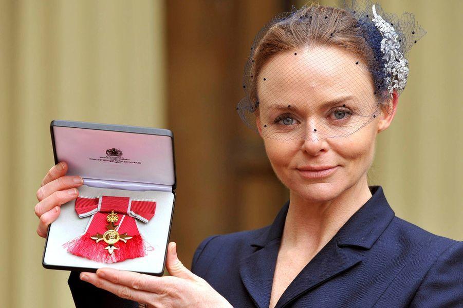 La fille de Sir Paul, styliste talentueuse, montre sa croix de l'Ordre de l'Empire Britannique remise par la Reine le 26 mars 2013.