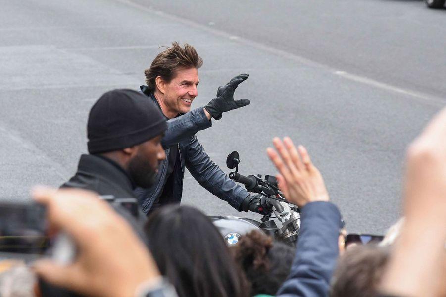 Tom Cruise sourit aux passants.