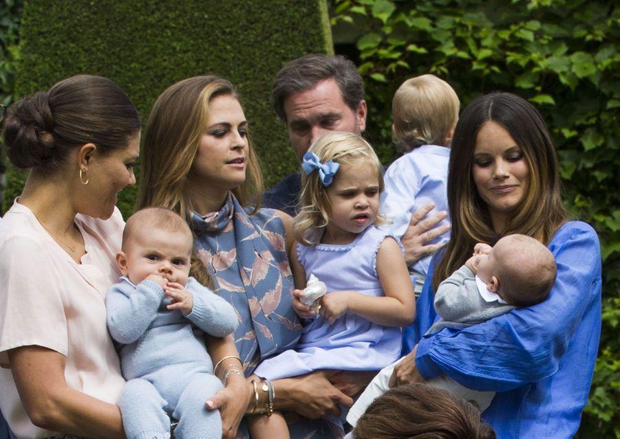 La princesse Victoria berce son dernier enfant, Oscar, pendant que la princesse Leonore regarde, intriguée, son petit cousin Alexander, dans les br...