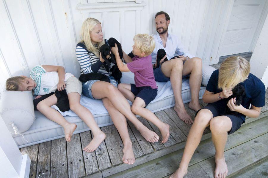 En vacances dans leur maison de Dvergsoya, en Norvège, Mette-Marit, Haakon et leurs enfants Marius, Ingrid Alexandra et Sverre Magnus ont profité de leur chienne Milly Kakao et de ses adorables chiots. Des animaux câlinés et choyés comme il se doit par la famille princière.