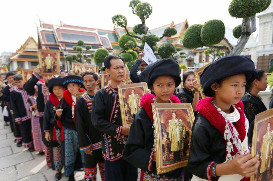 Les Thaïlandais en costume traditionnels, attendent pour rendre un dernier hommage au roi Bhumibol à Bangkok, le 29 octobre 2016
