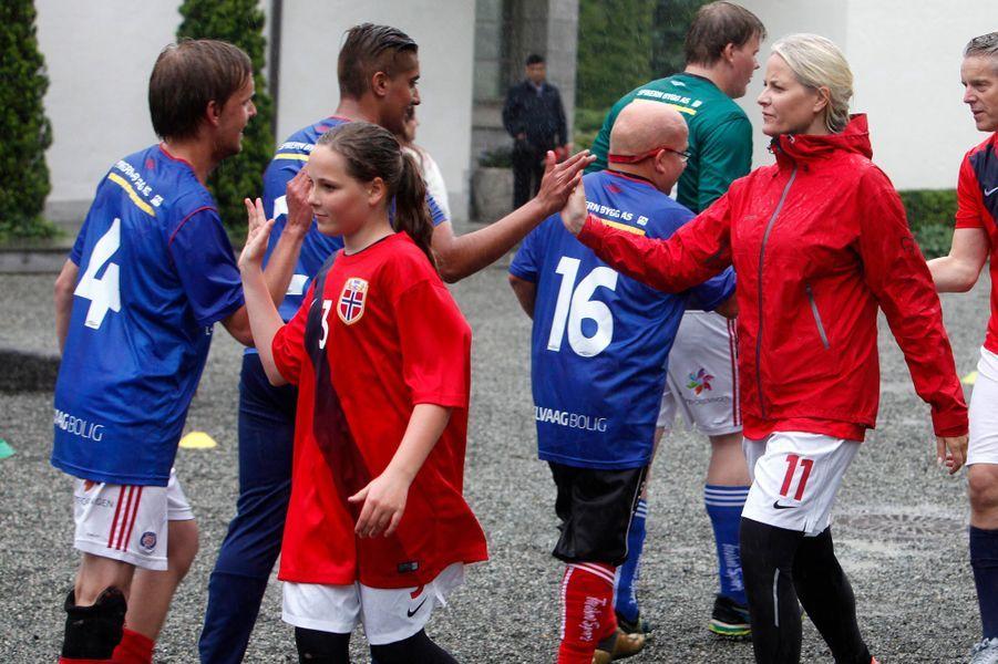 Ce lundi 20 juin, c'est sous la pluie que la princesse Ingrid Alexandra de Norvège a participé, avec son petit frère le prince Sverre Magnus et leurs parents Mette-Marit et Haakon, à un match de football solidaire.
