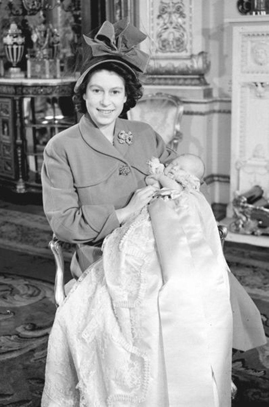 Charles dans les bras de sa mère Elizabeth, avec la même robe qu'elle portait à son baptême, le 15 décembre 1948