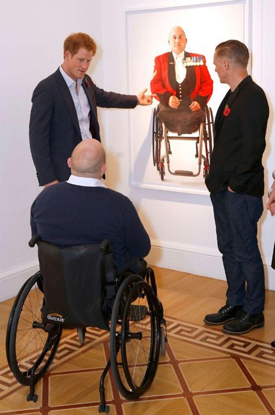 Le prince Harry visite l'exposition de photographies de militaires blessés de Bryan Adams à la Somerset House à Londres, le 11 novembre 2014