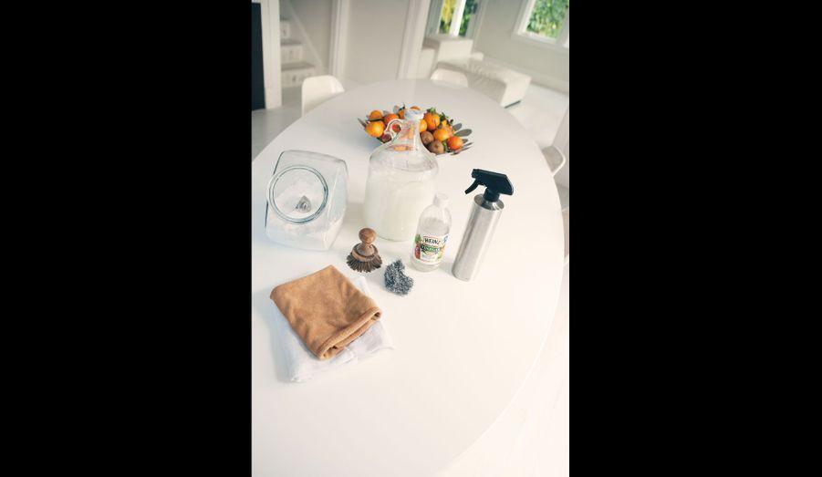 Tout ce qui lui sert à faire le ménage tient sur cette table: lessive achetée en vrac, savon liquide fait maison stocké dans une grande bouteille, vinaigre d'alcool pour remplacer tous les détergents, chiffon en microfibre pour laver et essuyer.