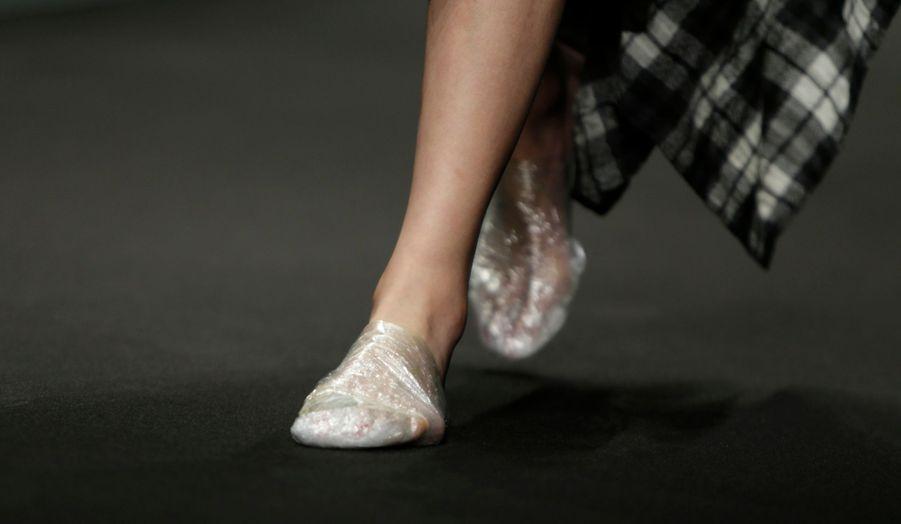 Un mannequin défile lors de la fashion week de Pékin, pour la marque Just for Tee. Les chaussures sont faites de... cellophane.