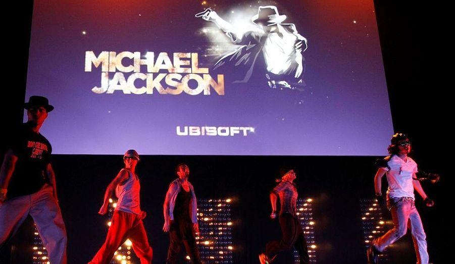 """Il ne manquait plus qu'un jeu vidéo au business Michael Jackson, c'est maintenant chose faite. Le """"King of Pop"""" sera l'objet d'un jeu de danse et de karaoké qui sortira sur la Wii et la Xbox 360, rapporte le site TMZ . Le principe est simplissime : alors que Michael Jackson chantera et dansera à l'écran, il faudra que le joueur en fasse de même devant sa télévision. La version Xbox 360 sera d'ailleurs équipée du système Kinect, de Microsoft, qui permet de jouer sans manette. Le jeu sera mis en vente en décembre 2010. Ici, des danseurs se sont produits pour la présentation du jeu """"Michael Jackson"""" lors du congrès Ubisoft Media à Los Angeles."""