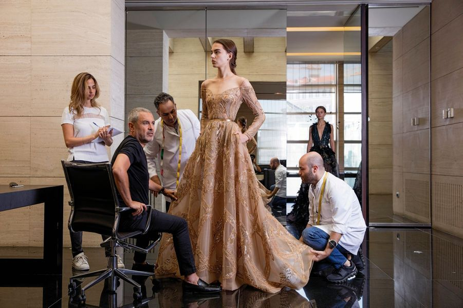 Elie Saab avec ses assistants Cybele, Marwan et Patrick (à dr.), dans son atelier à Beyrouth, le 23 juin. Robe en tulle or antique, arabesques brodées de fils métallisés, de sequins et de perles.