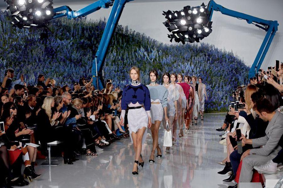 Dans la cour Carrée du Louvre, le final du défilé Dior. En tête, le mannequin porte un pull court festonné en jacquard de laine bleu cobalt sur une robe chemise en voile de coton.Un champ de 400000 delphiniums et une forêt de Smartphone. Si le réseau est saturé autour des podiums, c'est que les créateurs conviés à la Fashion Week ne manquent pas d'inspiration. Avec une collection «singulièrement futuriste et étrangement romantique», Raf Simons a donné le ton pour cette semaine de shows spectaculaires relayés dans le monde entier sur les réseaux sociaux. En plein mois d'octobre, la capitale française a décliné le printemps prochain en 91 défilés et une promesse: le pouvoir de séduction revient en force avec une mode ultra féminine. Alors que la femme fleur de Dior dégage pureté et simplicité, la dame de fer choisit le clinquant: pendant huit jours, la tour Eiffel a affiché «La mode aime Paris».Justicière de l'espace aux cheveux roses tout droit sortie de studios d'animation japonais, tribu de nomades aux crêtes iroquoises acidulées, gladiatrices aux cuissardes en vinyle… Quand la mode rencontre la technologie et l'univers numérique, les enseignes de prêt-à-porter mêlent l'esthétique des jeux vidéo ou des dessins animés aux codes vestimentaires de la rue. Avant-garde et influences rebelles venues du punk ou du rock. Un cocktail détonant pour figurer des héroïnes modernes.Echappée belle porte «N°5»… Quand Karl Lagerfeld prend les commandes de la «Chanel Airlines», le Grand Palais devient l'aéroport «Paris Cambon», temple de l'escale aérienne. Entre les comptoirs d'enregistrement et les bancs métalliques, circulent des vacancières sophistiquées mais décontractées, casquettes à l'envers ou chemises nouées autour de la taille. «J'aime cette idée de vêtements faits de matières très riches, et portés comme du streetwear», dit le couturier. Les passagères du terminal «2C» sont les ambassadrices d'une exigence bleu, blanc, rouge. L'élégance et le confort d'un long voyage en p