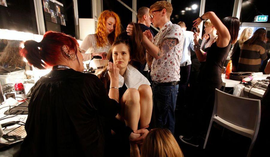 Pendant leur préparation, les modèles rêvent, discutent ou passent le temps en écoutant de la musique via leur téléphone portable.