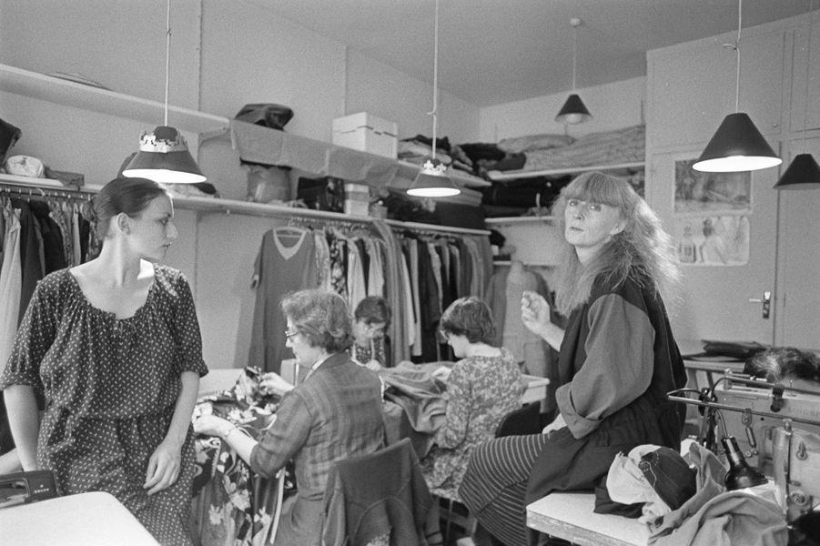 La créatrice Sonia Rykiel, assise sur une table, parmi ses couturières et collaboratrices dans son atelier rue de Grenelle.
