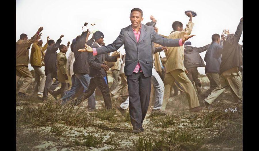 Un homme désemparé lève les mains au ciel devant des centaines de réfugiés maliens qui manifestent.