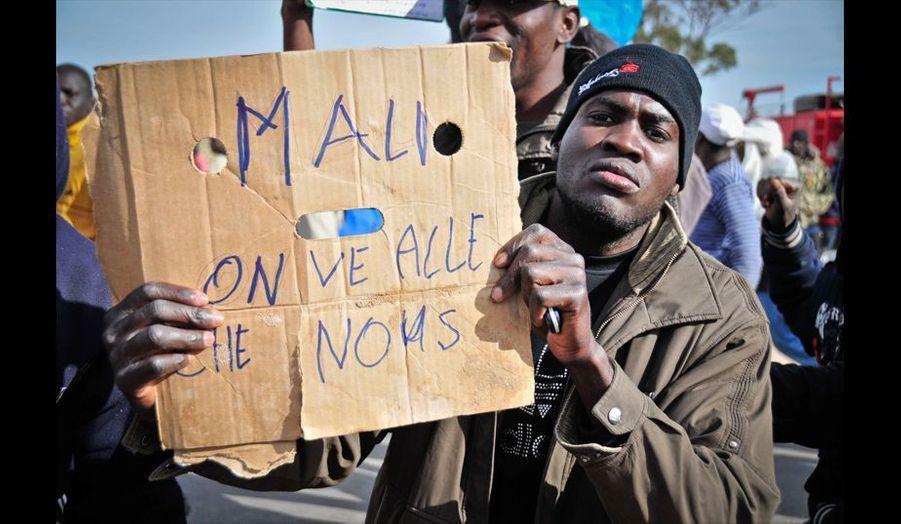 Un réfugié malien improvise une pancarte sur un bout de carton pour manifester et exprimer son désir d'être rapatrié.
