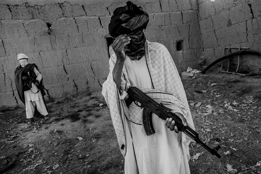 A member of Taliban covering his face from the photographer, Ghondouz city, North of Kabul