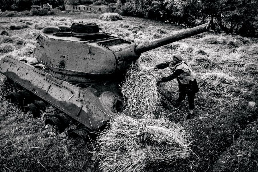 A farmer puts his harvest on a tank left behind in war. The effect of 30 years of war is visible throughout most of the country, and the people have gotten used to living with these ruins.
