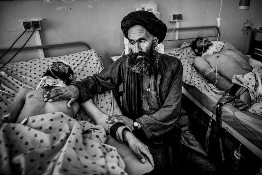 An Afghan man sitting beside his injured son by Taliban attack in Kandahar, treated in Mirvays Hospital after killing of Bin laden, in Pakistan,it was the most serious attack by his supporters lead to 4 killed and 36 injured.