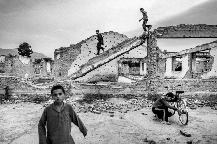 Afghan boys play in the ruins from war in center of Kabul.