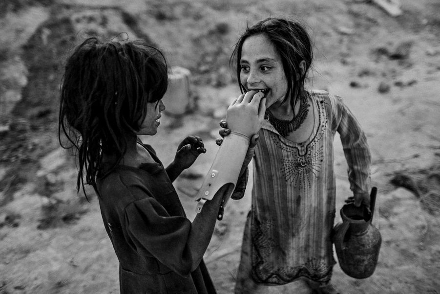 Two Afghan girls play with an artificial hand, south of Kabul.