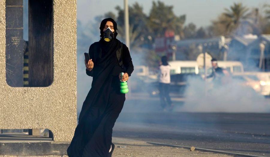 Une femme, équipée d'un téléphone portable, d'un diffuseur et masque à gaz, fuit les gaz lancés par les forces de l'ordre lors d'une manifestation à Diah, au Bahreïn.