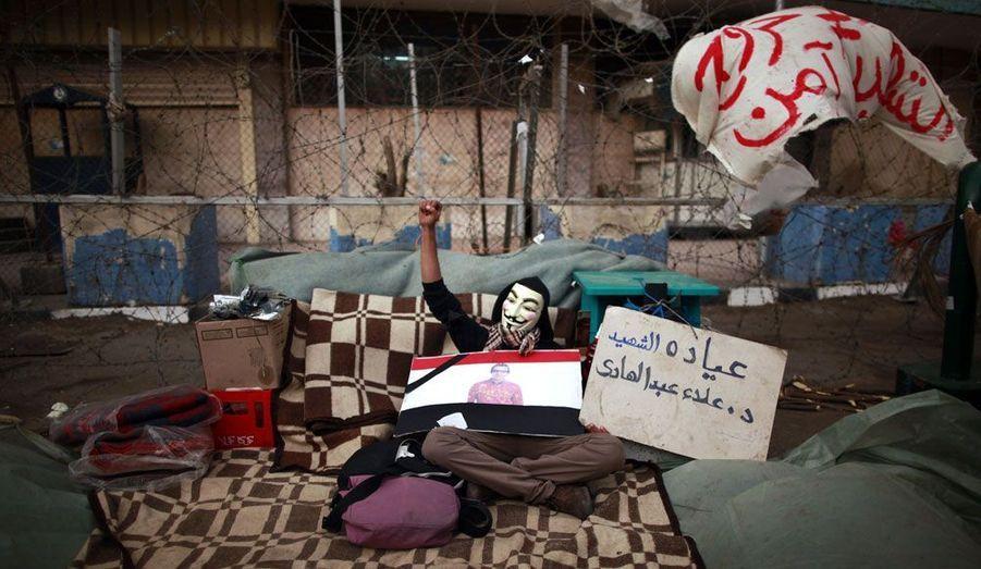 """Installé devant les locaux de la télévision d'état égyptienne au Caire, un manifestant caché par un masque du groupe «Anonymous» demande à l'armée de redonner le pouvoir au peuple. Il demande également, comme des milliers d'autres protestataires, une """"épuration"""" des médias, accusés de tout faire pour monter la population contre les manifestants."""