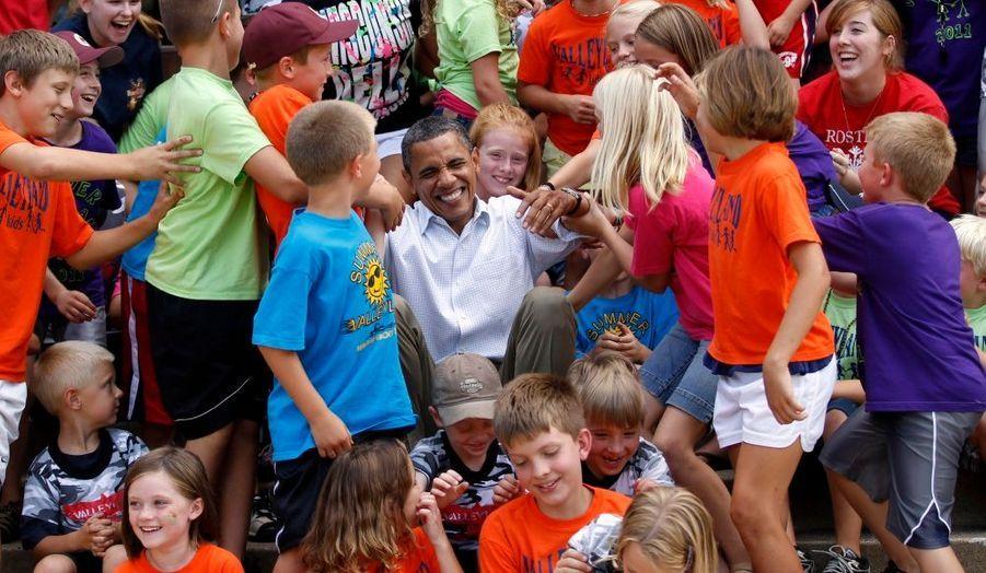 Des enfants scolarisés à Chatfield (Minnesota) aident Barack Obama à se relever après avoir posé avec lui pour une photo, lors de sa tournée dans le Midwest.