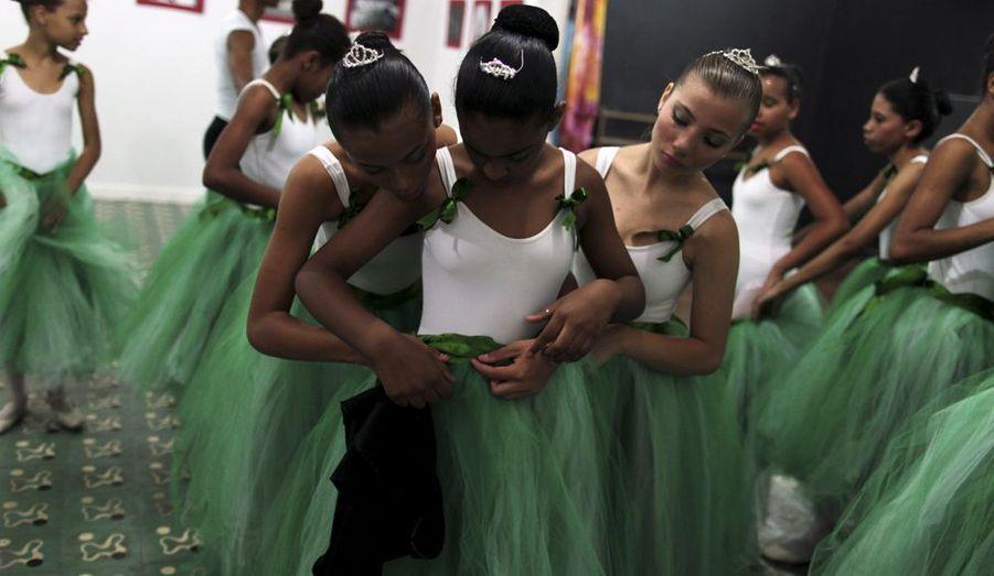 """Des danseuses brésiliennes aident l'une des leurs à ajuster sa tenue avant une séance d'entraînement. La particularité du """"Ballet Santa Teresa"""" de Rio de Janeiro, est d'offrir à des jeunes en difficulté des cours gratuits."""