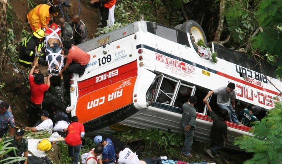 Les secouristes transportent un des passagers du bus tombé dans un ravin de cinquante mètres à Sablan, dans la province de Benguet, au nord des Philippines, ce matin. Le chauffeur aurait perdu le contrôle de son véhicule. On compte 41 morts.
