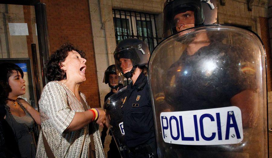 A Madrid, une manifestante mécontente du prix de la venue du Pape dans le cadre des JMJ prend à partie un policier.