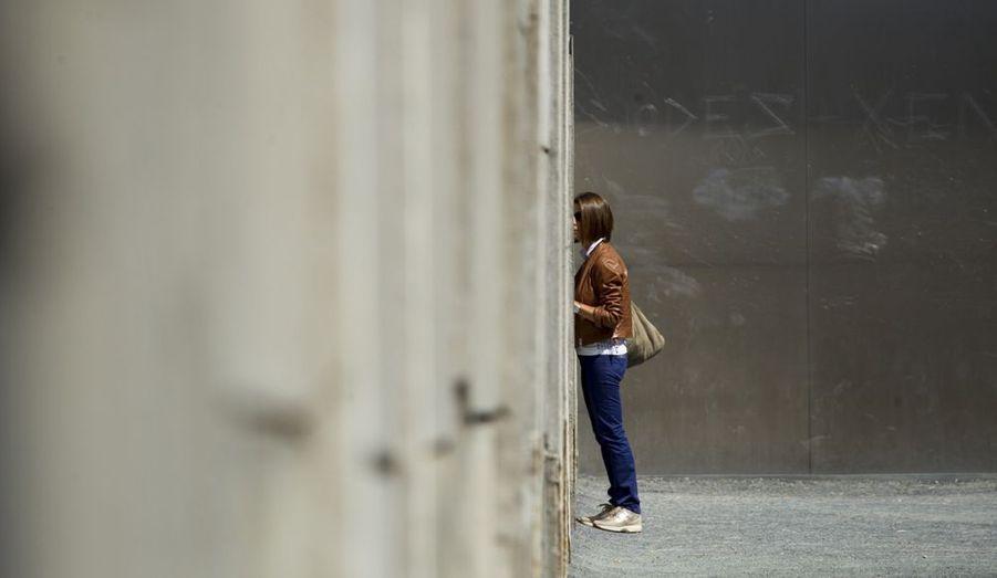Cette femme regarde à travers une fissure dans le béton d'une partie du mur de Berlin, sur le site mémorial de la Bernauer Strasse, à Berlin. Les 12 et 13 août, les Allemands commémoraient les 51 ans de la construction du mur, qui a séparé la ville en deux, de 1961 à 1989.