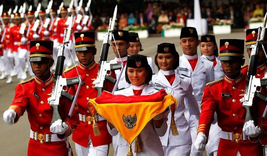 Une élève porte le drapeau national indonésien pendant une cérémonie de commémoration en présence du président President Susilo Bambang Yudhoyono pour célébrer le 65eme anniversaire de l'Indépendance au palais de Jakarta.