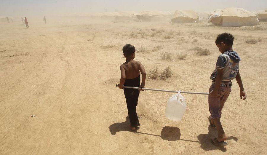 Deux enfants syriens rapportent de l'eau pour leur famille, dans le camp de réfugiés Al Zaatri, dans la ville de Mafraq, en Jordanie.