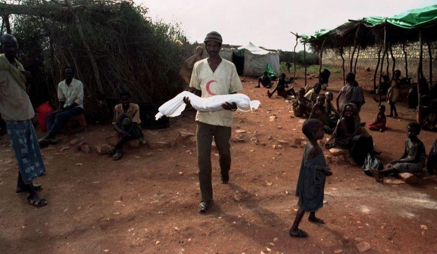 Un travailleur humanitaire porte un enfant mort dans le camp de réfugiés de Baidoa, en Somalie, en décembre 1992.