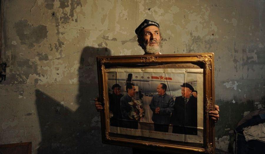 Un représentant de l'ethnie des Ouïgours, dans la province du Xinjiang, en Chine, montre un tableau historique sur la rencontre entre Zhou Enlai et Mao Zedong à Aksu, l'une des principales villes de la région. De croyance musulmane, les Ouïgours ne peuvent pratiquer le Ramadan.