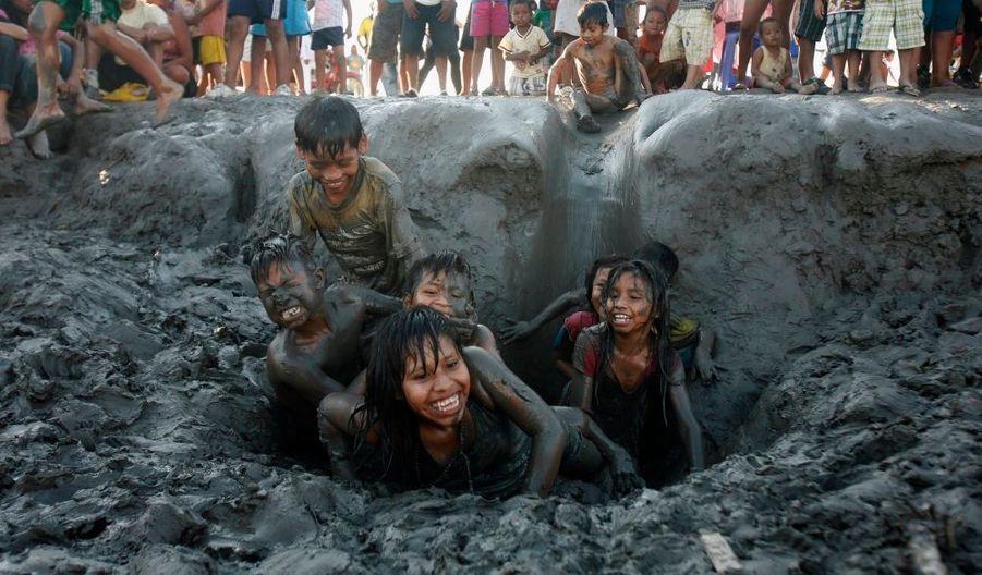 Des enfants jouent dans la boue pour fêter la désignation du fleuve Amazonie comme l'une des merveilles du monde, à Iquitos, au Pérou.