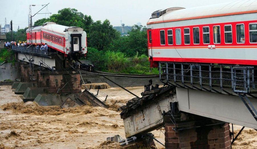 Un pont de chemin de fer a été partiellement détruit par les inondations, entraînant la chute de deux wagons dans la rivière de Guanghan Xiaohan, située dans la province du Sichuan, hier. Les passagers chinois ont pu être évacués à temps.