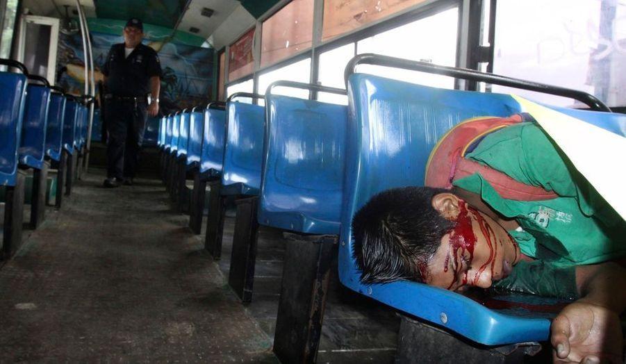 Un officier de police dans un bus de la station balnéaire d'Acapulco, auprès d'un homme abattu par un gang.