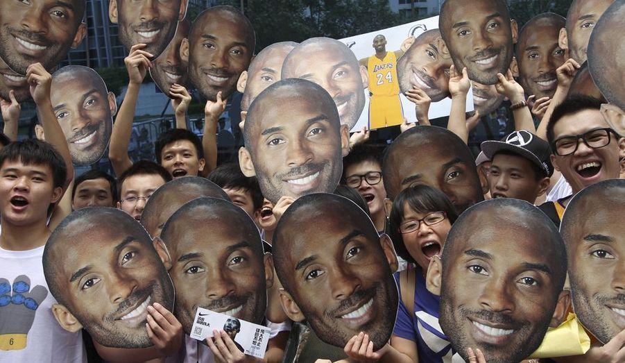 Une horde de fans agitent des masques du basketteur américain Kobe Bryant. Celui-ci est en tournée promotionnelle à Guangzhou, dans la province de Guangdong, en Chine.